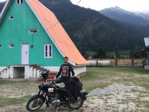 Malkit posing with bike at alpine hut guest house Gulabgah